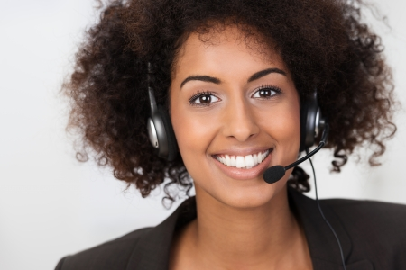 Close up facial portrait of a beautiful vivacious African American businesswoman wearing a headset smiling at the camera conceptual of client services, support or a call centre operator