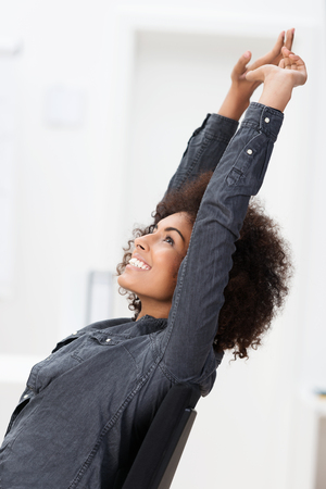 jubilation: Excited African American businesswoman smiling in jubilation and raising her arms in the air as she relaxes in her chair at the office Stock Photo