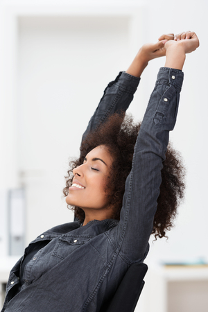 African American businesswoman relaxing at work reclining back in her chair stretching her arms in the air and closing her eyes in contentment photo