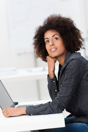 Young African American businesswoman seeking inspiration sitting at her desk in front of her laptop looking upwards with a pensive smile as she looks for a solution photo