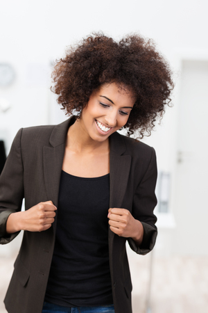 lapels: Natural photo of a happy laughing young African American woman with a frizzy afro hairstyle holding her lapels and looking down in amusement Stock Photo
