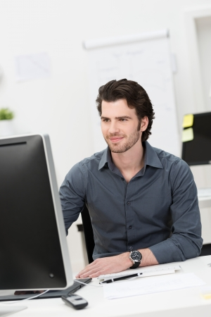 Handsome young businessman working at his desktop computer sitting at his desk in the office photo