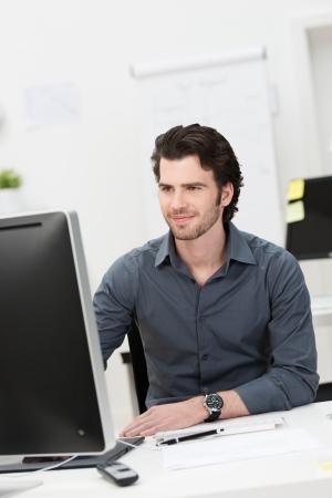 Knappe jonge zakenman werken op zijn desktop computer zit aan zijn bureau in het kantoor Stockfoto