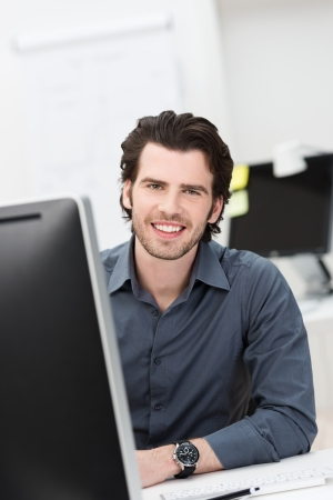 administracion de empresas: Hombre de negocios confidente acertado con una cálida sonrisa sentado en su escritorio en la oficina mirando a la cámara Foto de archivo