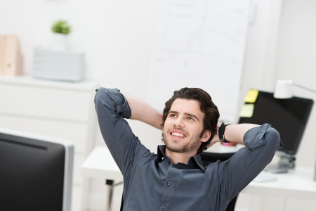 Successful businessman relaxing in his chair leaning back with his hands behind his head looking into the air smiling Stock Photo