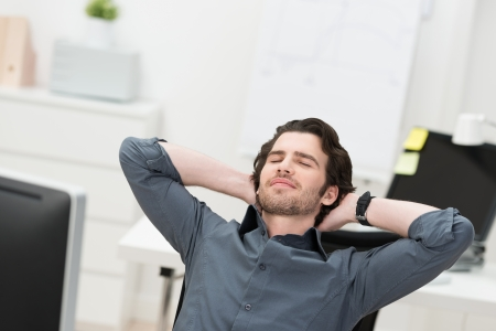 Businessman taking a break at his desk leaning back in his chair with closed eyes and his hands clasped behind his head photo