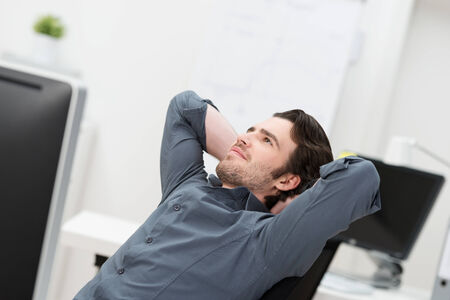 hands behind back: Businessman sitting daydreaming at his desk at the office leaning back in his chair looking up into the air with a pleased thoughtful smile and his hands clasped behind his head Stock Photo