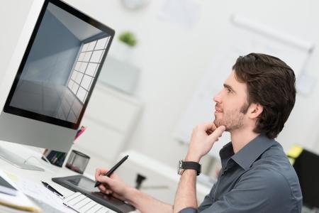 Uomo d'affari con una tavoletta e penna per navigare sul suo computer desktop in ufficio seduto di profilo il pensiero e la lettura del monitor