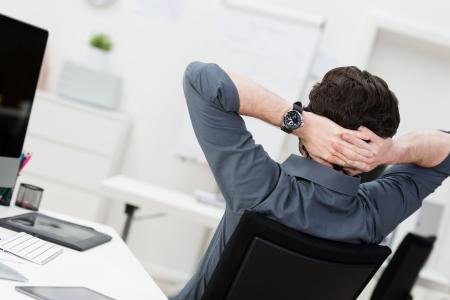 hombre sentado: Empresario Lazy relax en la oficina sentado atrás con las manos detrás de la cabeza, ángulo de visión trasera Foto de archivo
