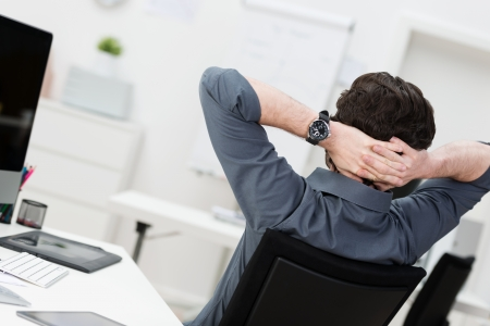 back up: Lazy businessman relaxing at the office sitting back with his hands behind his head, rear angle view