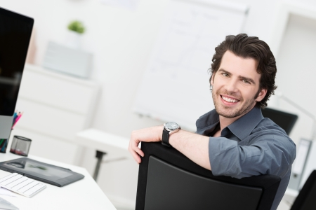 Smiling young businessman sitting in his office turning to look at the camera over the back of his chair photo