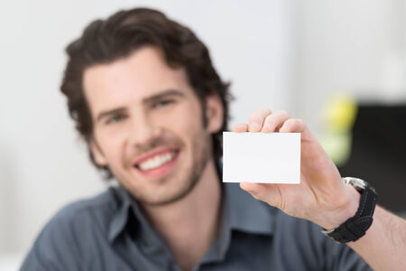Handsome young businessman with a lovely friendly smile holding up his blank white card card to show his credentials and qualification