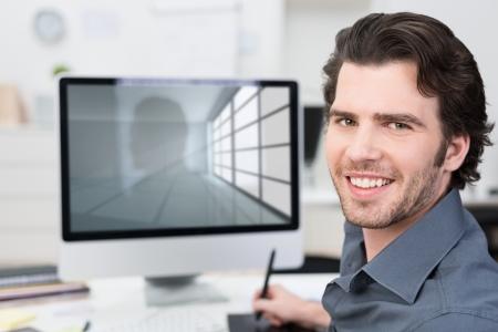 사업가 카메라에 미소를 보이는 화면 외면 타블렛과 스타일러스를 사용하여 자신의 컴퓨터로 작업