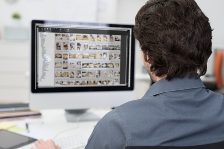 View from behind over his shoulder of a photographer editing photos on a computer with rows of images visible on the monitor Stock Photo
