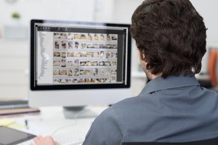 usando computadora: Vista desde atrás por encima del hombro de un fotógrafo de la edición de fotos en un ordenador con hileras de imágenes visibles en el monitor