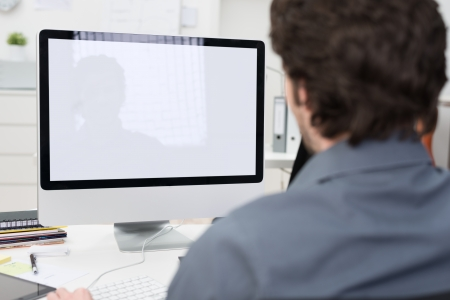 computer user: Businessman using a desktop computer with a view over his shoulder from behind of the blank screen of the monitor Stock Photo