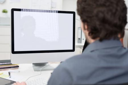 usando computadora: Hombre de negocios usando un ordenador de sobremesa con una vista por encima del hombro por detrás de la pantalla en blanco de la pantalla Foto de archivo