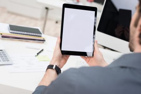볼 빈 흰색 화면 태블릿 컴퓨터를 사용하여 자신의 책상에 앉아 젊은 사업가의 어깨 너머로보고 스톡 콘텐츠