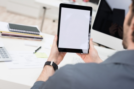 viewable: Looking over the shoulder of a young businessman sitting at his desk using a tablet computer with the blank white screen viewable