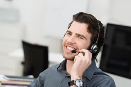 hands free: Hombre de negocios usando un auricular para la comunicaci�n manos libres o un joven operador de centro de llamadas de tomar una llamada al servicio de asistencia Foto de archivo