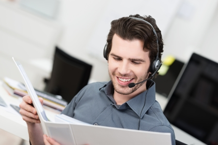 happy young man: Call centre operator or client services businessman wearing a headset looking up information in a file in order to be of assistance to the client