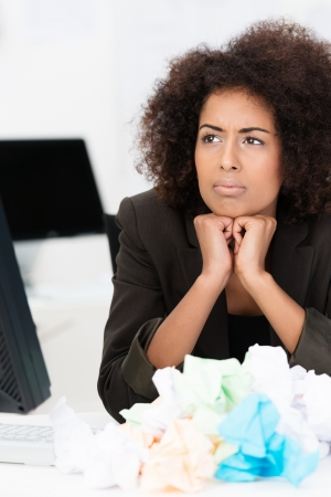 writers block: African American businesswoman in trouble suffering from writers block or lack of imagination in solving a business problem surrounded by a heap of crumpled paper