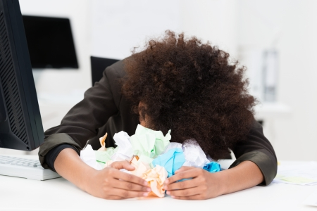 Distraught writer or businesswoman with her head lying on her desk in a pile of crumpled paper as she suffers from writers block or a total inability to come up with a solution to a problem