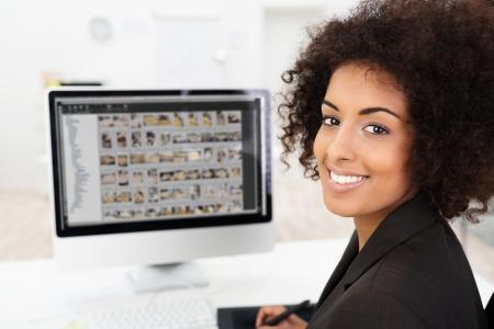 Lachend African American zakenvrouw bewerken van foto's zichtbaar op haar computerscherm als ze draait om lachen naar de camera