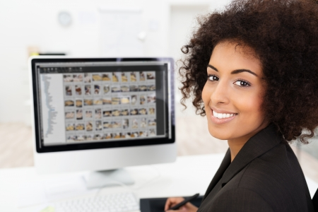 presentation screen: Smiling African American businesswoman editing photographs visible on her computer screen as she turns to smile at the camera