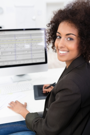 African American businesswoman doing a spreadsheet using a tablet and stylus with her desktop computer turning to smile at the camera Banco de Imagens