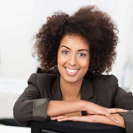 Beautiful young African American businesswoman with a cute frizzy hairdo and a lovely smile sitting with her arms folded on her desk looking at the camera
