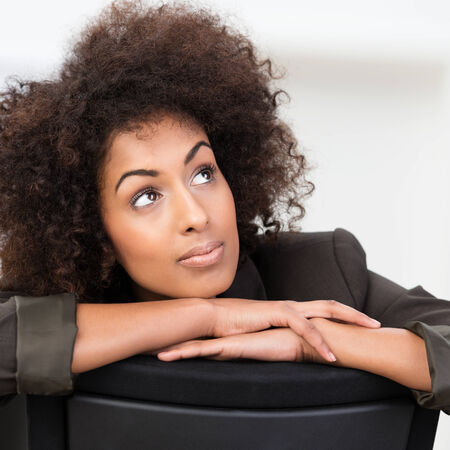 Pensive African American businesswoman with curly afro hair sitting with her arms on the back of the chair staring up into the air in contemplation photo