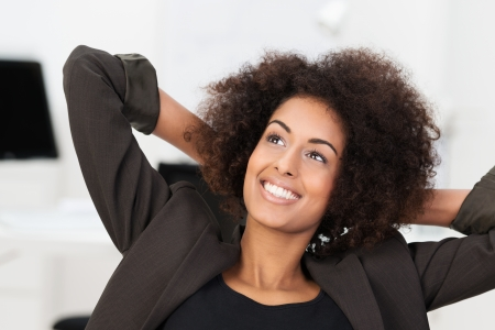 contentment: Beautiful African American businesswoman smiling as she relaxes in her chair at the office leaning back with her hands behind her head and a look of pleasurable contentment