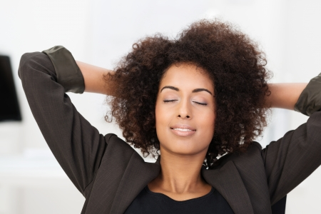 African American businesswoman taking a break at the office sitting with her hands clasped behind her head and her eye closed in relaxation Stock Photo - 25337145