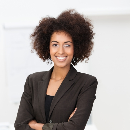 Beautiful young vivacious African American businesswoman in a stylish jacket standing with her arms folded beaming at the camera photo
