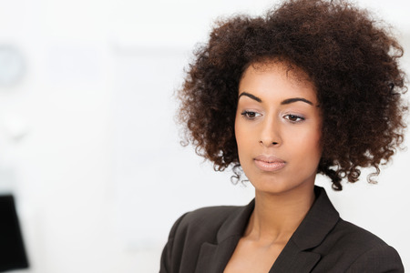 withdrawn: Sad wistful African American businesswoman staring downwards with a calm withdrawn expression, head and shoulders portrait on white