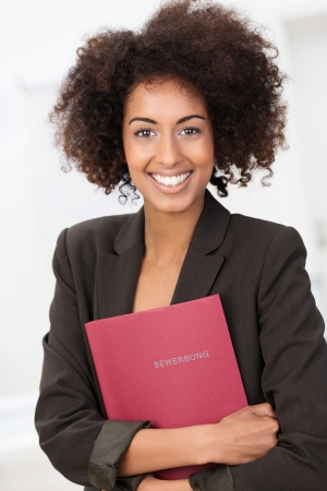 Beautiful young African American woman with a curly afro hairstyle clutching a red file looking at the camera with a vivacious happy smile photo