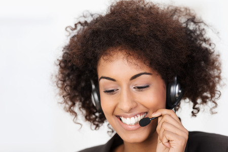 warmly: Friendly African American call centre operator wearing a headset in her curly hair smiling warmly as she listens to the conversation while helping a client Stock Photo