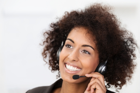 helpdesk: Beautiful vivacious young African American client services, call centre operator or receptionist smiling a warm friendly natural smile as she listens to a client speaking on her headset Stock Photo