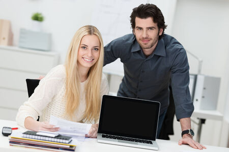 advertisment: Young businessman and woman in the office sitting at a desk with their laptop screen turned to face the camera with copyspace for your text or advertisement