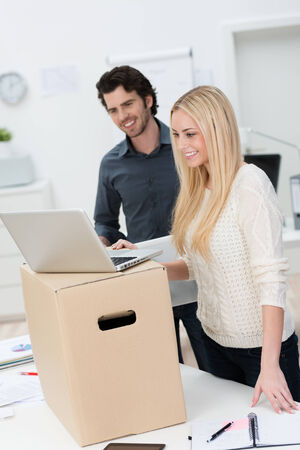 Two attractive young business partners moving into new offices smiling with satisfaction as they set up a laptop computer on top of a cardboard carton photo