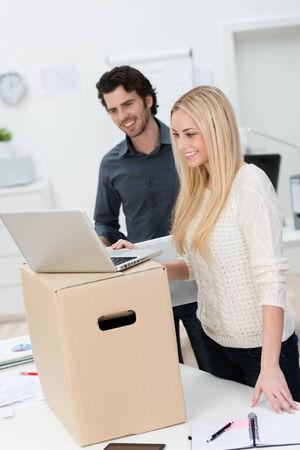 Deux jolies jeunes partenaires d'affaires se déplaçant dans de nouveaux bureaux en souriant avec satisfaction comme ils mis en place un ordinateur portable sur une boîte en carton