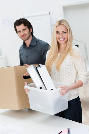 moving office: Smiling businesswoman moving into a new office assisted by a handsome male colleague as they carry across her files and possessions in boxes Stock Photo