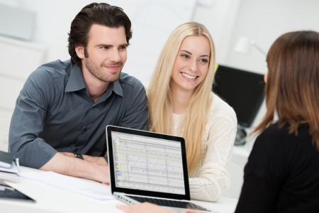 Investment or insurance broker or adviser conducting an interview with a smiling young couple as they plan their future investments photo
