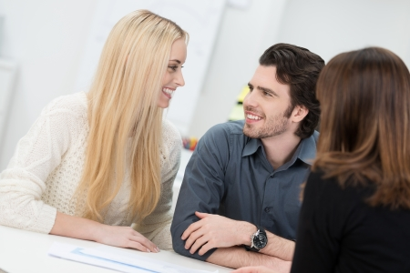 Happy couple looking at each other during in an interview in an office photo