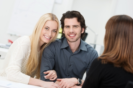 embraced: Happy couple embraced in an affectionate way during an interview Stock Photo