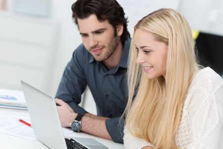 Business team consisting of a young man and woman sitting working together at a laptop and smiling as they access information on the screen