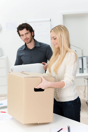 Young businesswoman moving into a new office carrying a large brown cardboard carton assisted by a male colleague photo