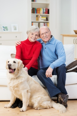 mature people: Affectionate happy relaxed senior couple sitting arm in arm on the sofa in their living room with their golden retriever dog Stock Photo