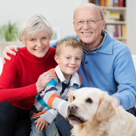Happy little boy with his elderly grandparents sitting close together on a sofa in the house patting a friendly loyal golden retriever dog photo
